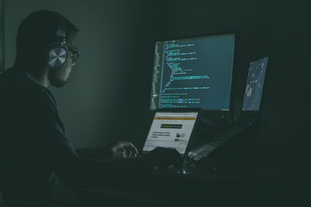 Person sat at a desk with a laptop, typing code, wearing headphones. Programming